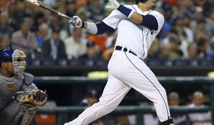 Detroit Tigers' Victor Martinez watches his two-run home run during the seventh inning of a baseball game as Kansas City Royals catcher Salvador Perez looks on at Comerica Park, Saturday, Sept. 19, 2015, in Detroit. (AP Photo/Duane Burleson)