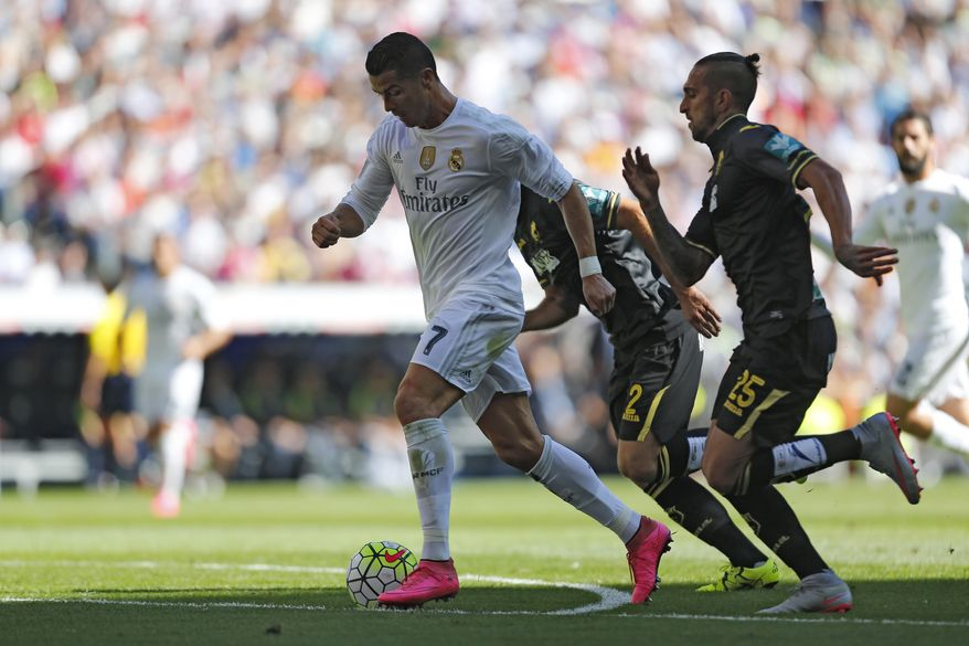 Real Madrid's Cristiano Ronaldo, left, tussles for the ball with Granada's Miguel Lopes during a Spanish La Liga soccer match between Real Madrid and Granada at the Santiago Bernabeu stadium in Madrid, Saturday, Sept. 19, 2015. (AP Photo/Francisco Seco)