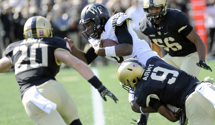 Wake Forest quarterback Kendall Hinton (2) is chased down by Army defensive back Rhyan England (20) defensive back Xavier Moss (9) and linebacker Kenneth Brinson (56) during the second half of an NCAA college football game on Saturday, Sept. 19, 2015, in West Point, N.Y. (AP Photo/Hans Pennink)