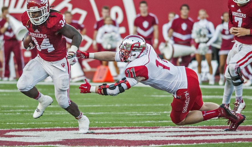 Indiana running back Devine Redding (34) evades a tackle attempt by Western Kentucky defensive lineman Tanner Reeves (11) during an NCAA college football game Saturday, Sept. 19, 2015, in Bloomington, Ind. (Austin Anthony/Daily News via AP)