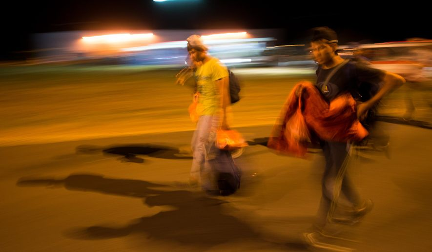 Migrants arrive at the border between Austria and Hungary near Heiligenkreuz, about 180 kms (110 miles) south of Vienna, Austria, Saturday, Sept. 19, 2015. Thousands of migrants who had been stuck for days in southeastern Europe started arriving in Austria early Saturday after Hungary escorted them to the border.  (AP Photo/Christian Bruna)