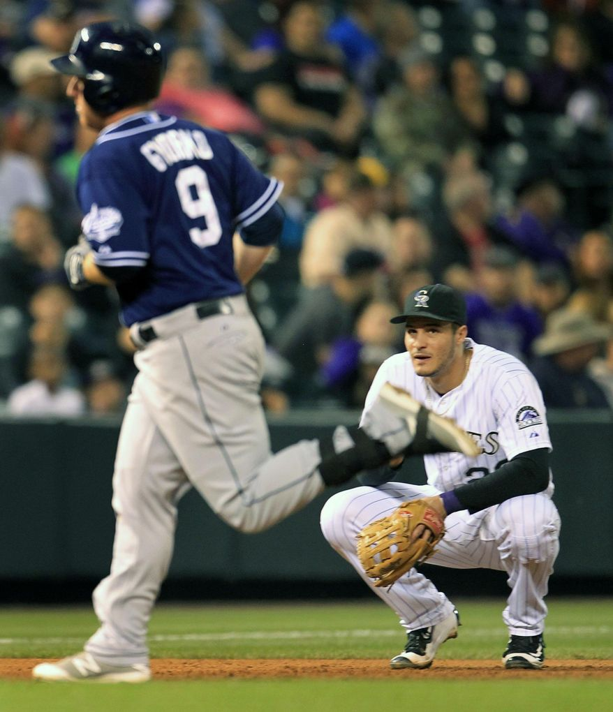Colorado Rockies third baseman Nolan Arenado (28) watches San Diego Padres' Jedd Gyorko (9) jog towards home after Gyorko's solo home run in the sixth inning of a baseball game in Denver on Saturday, Sept. 19, 2015.(AP Photo/Joe Mahoney)