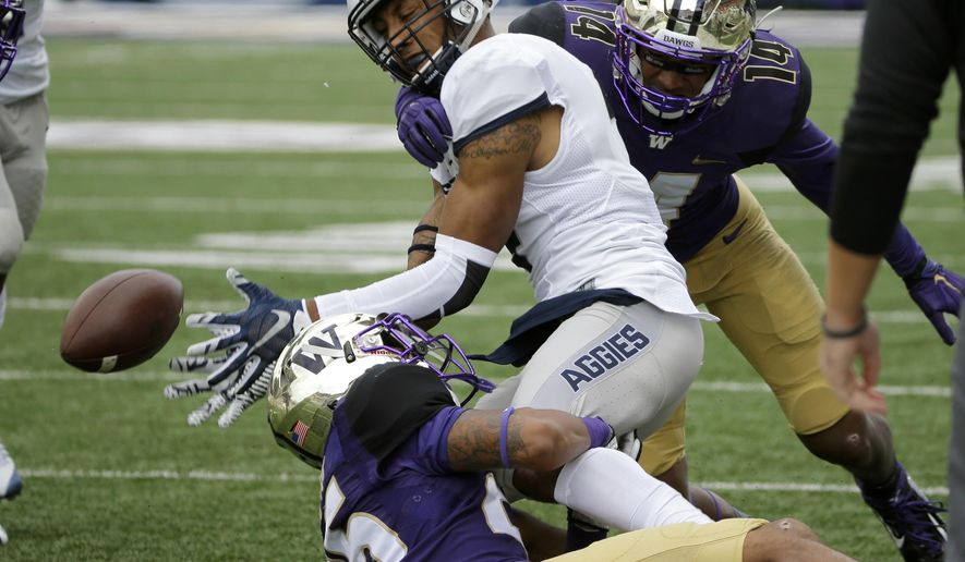 Utah State wide receiver Hunter Sharp, center, fumbles as he is tackled by Washington's JoJo McIntosh, right, and Sidney Jones, lower left, in the first half of an NCAA college football game, Saturday, Sept. 19, 2015, in Seattle. Utah State recovered the fumble. (AP Photo/Ted S. Warren)