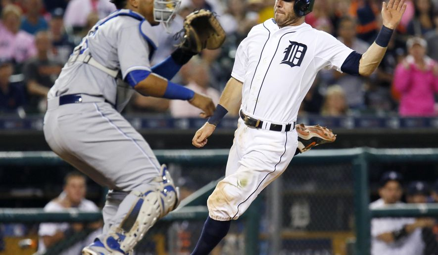 Detroit Tigers' Ian Kinsler scores from third base on a sacrifice fly ball hit by Victor Martinez as Kansas City Royals' Salvador Perez (13) waits for the ball during the eighth inning of a baseball game at Comerica Park Friday, Sept. 18, 2015, in Detroit. (AP Photo/Duane Burleson)