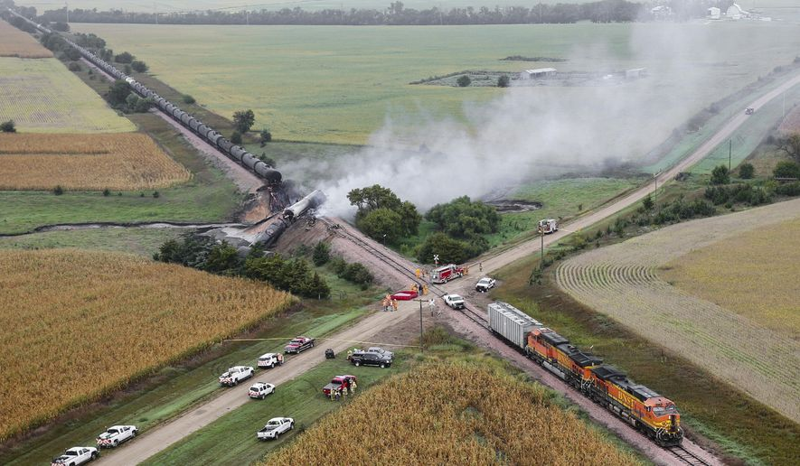 Smoke rises from a burning ethanol tanker car, Saturday Sept. 19, 2015, after the 98-car BNSF train carrying ethanol derailed in a rural part of Bon Homme County awash in corn fields between the towns of Scotland and Lesterville, S.D.  Three tankers were compromised and lost their contents. Officials aren't yet sure what caused the derailment over a small bridge that spans a dry creek. (Dave Tunge/Dakota Aerials via AP)