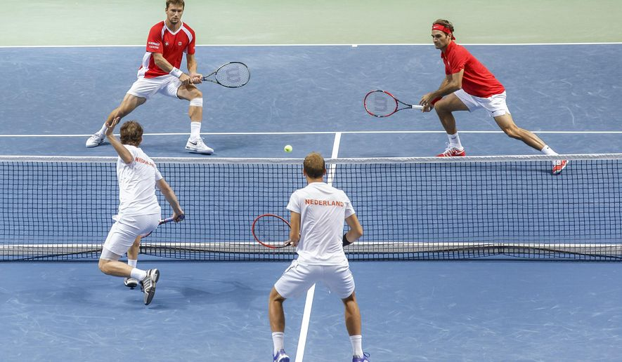Switzerland's  Marco Chiudinelli, top , left,  and his double partner Roger Federer, top right,   return a shot to Netherland Matwe Middelkoop, below left, and his double partner Thiemo De Bakker, below right,  return the ball, during the their double match of the Davis Cup World Group Play-off round match between Switzerland and Netherlands, at the Palexpo, in Geneva, Switzerland, Saturday, Sept. 19, 2015. (Salvatore Di Nolfi/Keystone via AP)