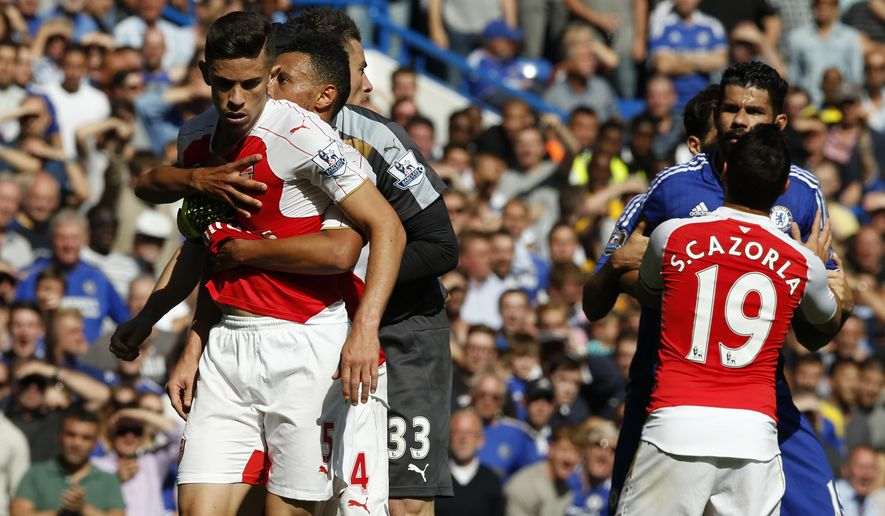 Arsenal's Gabriel, left is held by teammate Arsenal's Francis Coquelin after a clash with Chelsea's Diego Costa, second right, who is being moved away by Arsenal's Santi Cazorla during the English Premier League soccer match between Chelsea and Arsenal at Stamford Bridge stadium in London, Saturday, Sept. 19, 2015.  Arsenal's Gabriel was sent off later for a second clash with Costa, with Chelsea winning the match 2-0.(AP Photo/Alastair Grant)