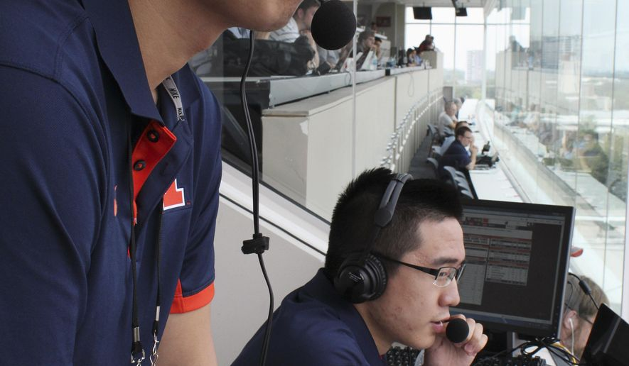 In this Sept. 5, 2015 photo, David He, left, and Bruce Lu broadcast a University of Illinois NCAA college football game from Memorial Stadium in Champaign, Ill. The two Illinois students are broadcasting Illini football games online in Mandarin Chinese this fall. (AP Photo/David Mercer)