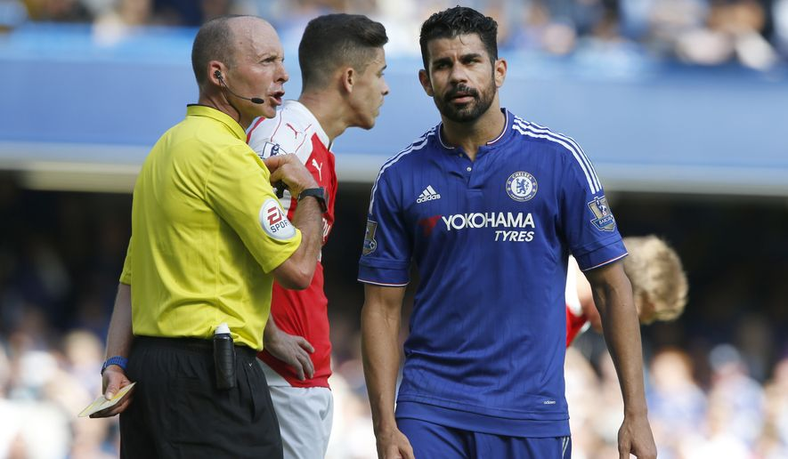 Referee Michael Dean holds a yellow cards after booking both Chelsea's Diego Costa, right, and Arsenal's Gabriel during the English Premier League soccer match between Chelsea and Arsenal at Stamford Bridge stadium in London, Saturday, Sept. 19 2015. Arsenal's Gabriel was sent off moments later for a further clash with Costa .(AP Photo/Alastair Grant)