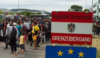 Migrants queue up for buses after they arrived at the border between Austria and Hungary near Heiligenkreuz, about 180 kms (110 miles) south of Vienna, Austria, Saturday, Sept. 19, 2015. Thousands of migrants who had been stuck for days in southeastern Europe started arriving in Austria early Saturday after Hungary escorted them to the border. (AP Photo/Christian Bruna)