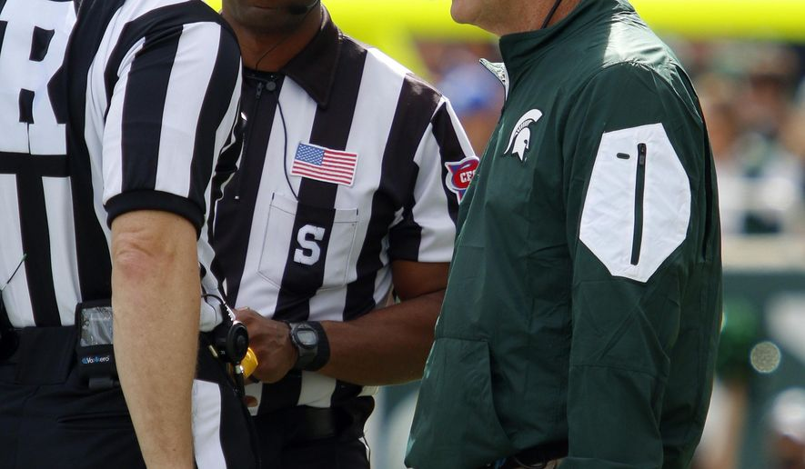 Michigan State coach Mark Dantonio, right, talks to officials Alan Eck, left, and A Flemming during the second quarter of an NCAA college football game against Air Force, Saturday, Sept. 19, 2015, in East Lansing, Mich. Michigan State won 35-21. (AP Photo/Al Goldis)