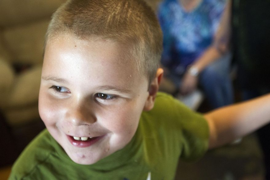 ADVANCED FOR RELEASE SATURDAY, SEPTEMBER 19, 2015 Elijah Walling, 8, smiles as he walks around the house with his braces on Tuesday, Sep 1, 2015, in Twin Falls, Idaho. (Drew Nash/The Times-News via AP)