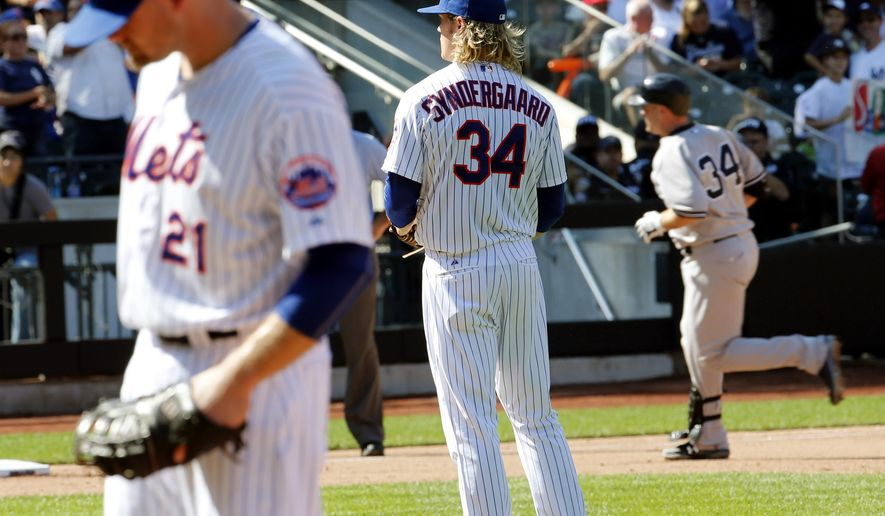 New York Yankees' Brian McCann, right, runs the bases after hitting a two run home run off New York Mets starting pitcher Noah Syndergaard, center, during the sixth inning of a baseball game, Saturday, Sept. 19, 2015, in New York. (AP Photo/Julio Cortez)