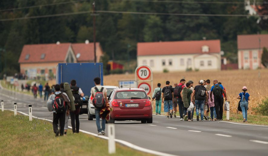 Migrants make their way along a road after crossing the border between Austria and Hungary near Heiligenkreuz, about 180 kms (110 miles) south of Vienna, Austria, in this Saturday, Sept. 19, 2015, file photo. (AP Photo/Christian Bruna)