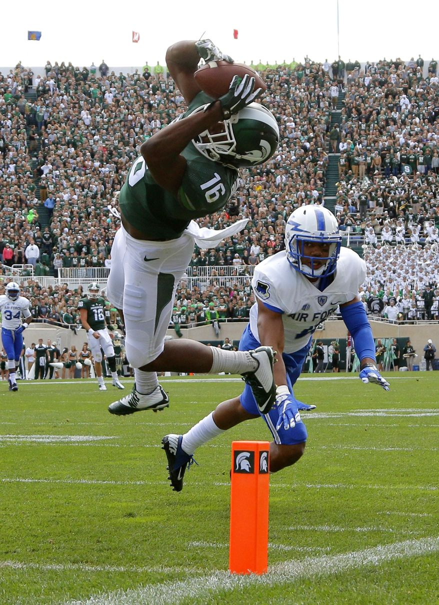 Michigan State's Aaron Burbridge, left, catches a pass for a touchdown against Air Force's Kalon Baker during an NCAA college football game, Saturday, Sept. 19, 2015, in East Lansing, Mich. (AP Photo/Al Goldis)