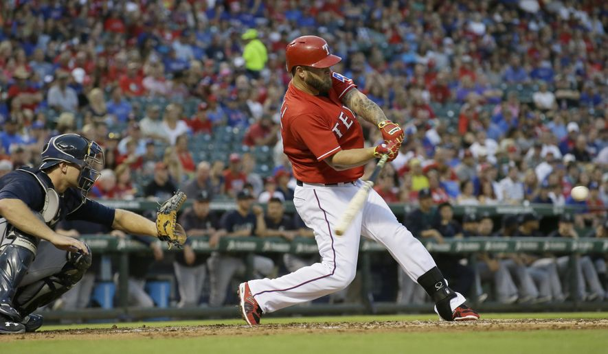 Texas Rangers Mike Napoli, right, hits an RBI-single in front of Seattle Mariners catcher John Hicks during the first inning of a baseball game in Arlington, Texas, Saturday, Sept. 19, 2015. Rangers' Shin-Soo Choo scored on the play. (AP Photo/LM Otero)