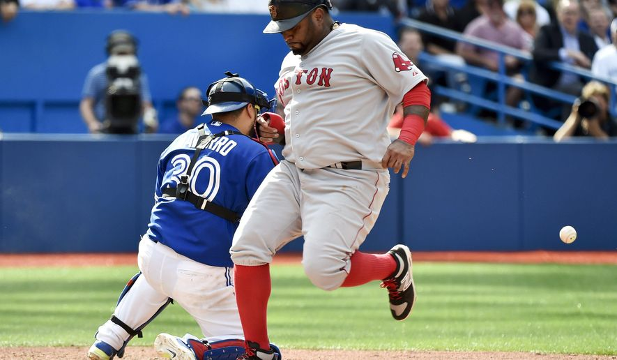 Boston Red Sox' third baseman Pablo Sandoval, right, scores the game winning run past Toronto Blue Jays' catcher Dioner Navarro at home plate during eighth inning of a baseball game, Sunday, Sept. 20, 2015 in Toronto. The Red Sox won 4-3. (Nathan Denette/The Canadian Press via AP) MANDATORY CREDIT
