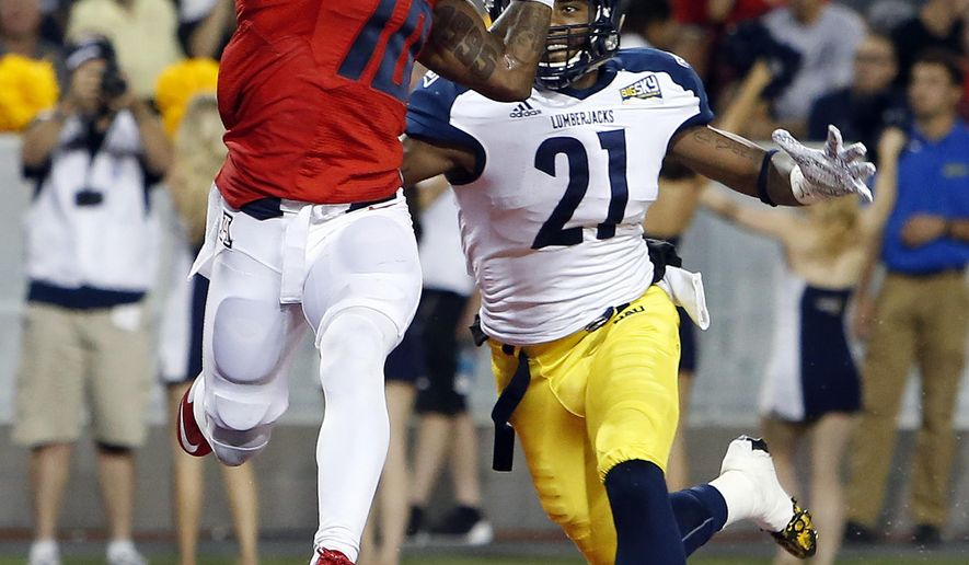 Arizona wide receiver Samajie Grant (10) catches a touchdown pass in front of Northern Arizona cornerback Delvin Batiste during the first half of an NCAA college football game, Saturday, Sept. 19, 2015, in Tucson, Ariz. (AP Photo/Rick Scuteri)