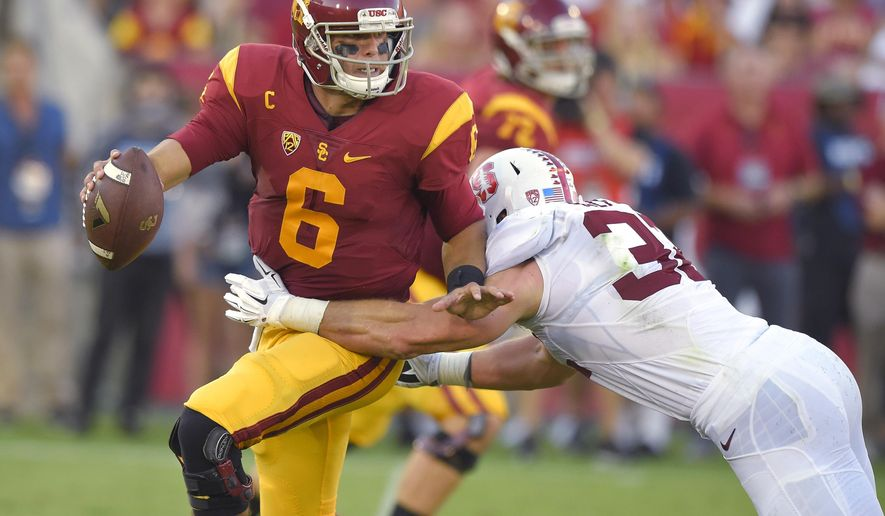 Southern California quarterback Cody Kessler, left, escapes a tackle by Stanford linebacker Joey Alfieri during the first half of an NCAA college football game, Saturday, Sept. 19, 2015, in Los Angeles. (AP Photo/Mark J. Terrill)