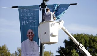 FILE - In this Wednesday, Sept. 16, 2015, file photo, a worker hangs banners ahead of Pope Francis' scheduled visit, on the Benjamin Franklin Parkway in Philadelphia. After months of angst over long security lines and onerous travel, organizers still expect more than a million people for Pope Francis' outdoor Mass in Philadelphia. (AP Photo/Matt Rourke, File)