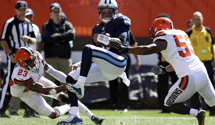 Tennessee Titans quarterback Marcus Mariota, center, is tackled by Cleveland Browns cornerback Joe Haden, left, and Craig Robertson during the first half of an NFL football game, Sunday, Sept. 20, 2015, in Cleveland. (AP Photo/Ron Schwane)
