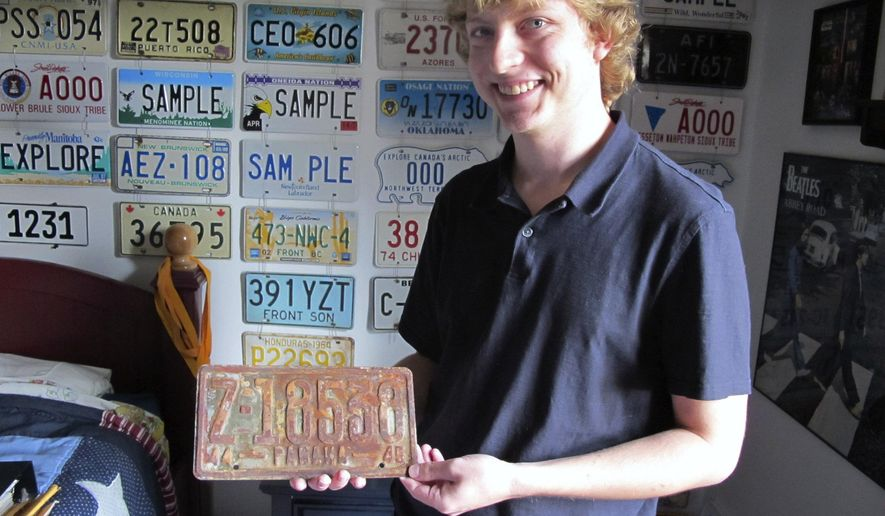 ADVANCE FOR MONDAY SEPT. 21 -In this Saturday Sept 5, 2015 photo  Andrew Braun shows off his extensive collection of international license plates, including this World War II era plate from the Panama Canal zone, at his home in Hurricane, W.Va. (Bill Lynch/Charleston Gazette Mail via AP) MANDATORY CREDIT