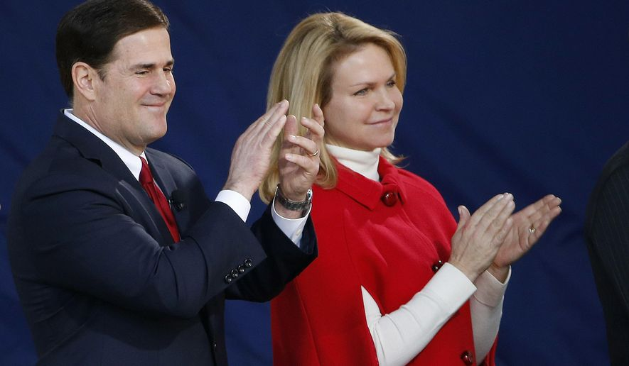 FILE - In a Jan. 5, 2015 file photo, Arizona Gov. Doug Ducey, applauds along with wife Angela Ducey as a choir sings during inauguration ceremonies at the Arizona Capitol, in Phoenix. Ducey, a life-long Catholic, was invited by President Barack Obama to meet the Pope Francis at the White House on Wednesday, Sept. 23. He's traveling with his wife to Washington for the White House event and then will be in attendance as Francis addresses a joint session of Congress on Thursday. (AP Photo/Ross D. Franklin, File)