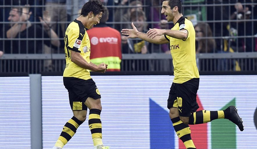 Dortmund's Shinji Kagawa, left, celebrates with teammate Henrikh Mkhitaryan after he scored his side's second goal during the German Bundesliga soccer match between Borussia Dortmund and Bayer Leverkusen in Dortmund, Germany, Sunday, Sept. 20, 2015. (AP Photo/Martin Meissner)