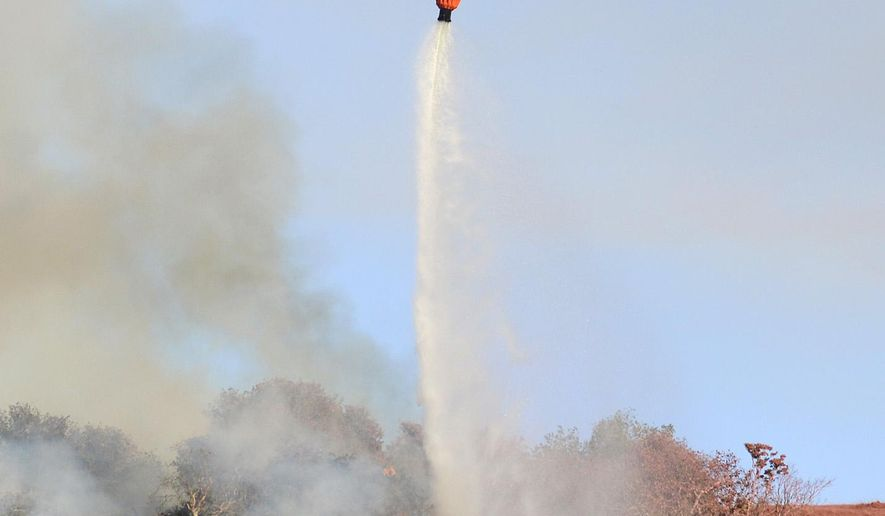 A helicopter drops water on a fire along Highway 68 east of Laureles Grade in rural Salinas, Calif., Saturday, Sept. 19, 2015. (David Royal/The Monterey County Herald via AP) MANDATORY CREDIT