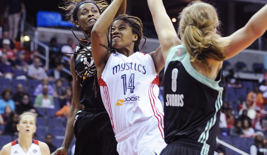 Washington Mystics' Emma Meesseman  (14) goes to the basket between New  York Liberty's Swin Cash(32) and Carolyn Swords (8) during an WNBA Eastern Conference basketball playoff game on Sunday, Sept. 20, 2015 in Washington. At left is Mytics' Emma Meesseman (33). (AP Photo/Kevin Wolf)