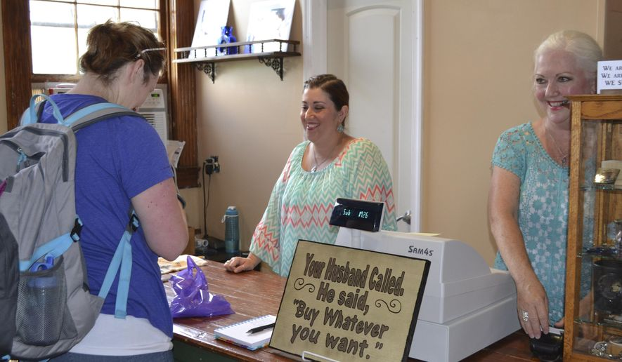 ADVANCE FOR MONDAY SEPT. 21 - This Sunday Sept. 6, 2015 photo shows Crystal Grimsley, manager of The Vintage Lady, and Cindi Dunn,right, owner, ring up Emily Montgomery at the store in Harpers Ferry, W.Va. The Vintage Lady reopened Saturday at a new location, as the former location was destroyed in the July 23 fire.  (Mary Stortstrom/The Journal via AP) MANDATORY CREDIT
