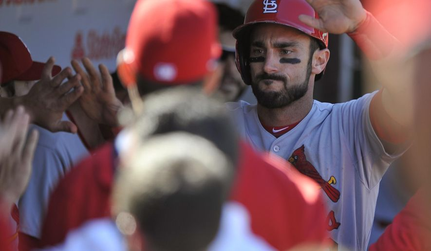 St. Louis Cardinals' Matt Carpenter  celebrates with teammates in the dugout after scoring on a Jhonny Peralta single during the third inning of a baseball game against the Chicago Cubs, Sunday, Sept. 20, 2015 in Chicago. (AP Photo/Paul Beaty)