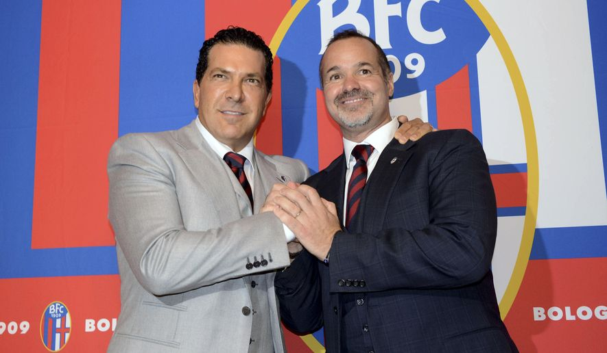 FILE - In this Thursday, Oct. 16, 2014 file photo Joe Tacopina, right, and Joey Saputo pose in front of the Bologna Football Club logo, in Bologna, Italy. New York lawyer Joe Tacopina has resigned as Bologna president following a rift with Canadian investor Joey Saputo, clearing the way for Saputo, already president of MLS club Montreal Impact, to also become Bologna's president. (AP Photo/Gianfilippo Oggioni, File)