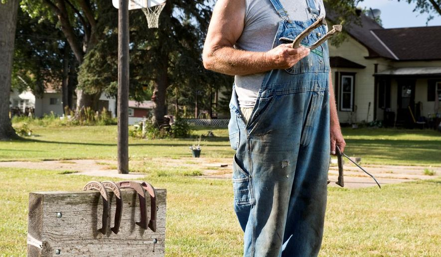 FOR RELEASE SUNDAY, SEPTEMBER 20, 2015, AT 12:01 A.M. CDT - In this Sept. 9, 2015 photo, horseshoe thrower Paul Mommens stands for a portrait outside his home in Worms, Neb. Mommens, who has been throwing horseshoes competitively for years, recently won his division at the World Horseshoe Tournament in Topeka Kan. (Matt Dixon/The Independent via AP) MANDATORY CREDIT