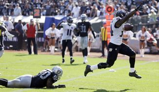 Baltimore Ravens' Lorenzo Taliaferro, right, runs in for a touchdown against the Oakland Raiders during an NFL football game Sunday, Sept. 20, 2015, in Oakland , Calif. (AP Photo/Ben Margot)