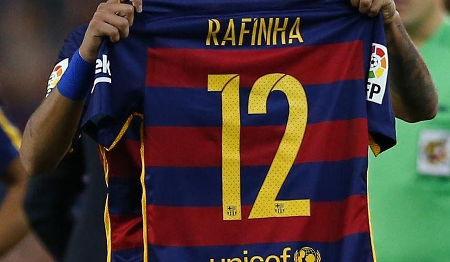 FC Barcelona's Neymar  holds the shirt of his teammate Rafinha after scoring against Levante during a Spanish La Liga soccer match at the Camp Nou stadium in Barcelona, Spain, Sunday, Sept. 20, 2015. (AP Photo/Manu Fernandez)