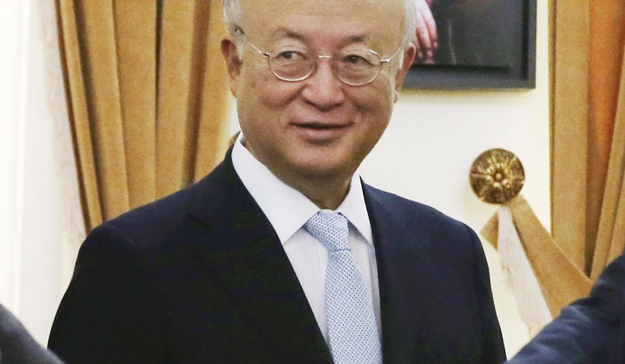 "FILE - In this July 2, 2015 file photo, U.N. nuclear chief Yukiya Amano stands as Secretary of Iran's Supreme National Security Council Ali Shamkhani shakes hands with delegation members before the start of their meeting in Tehran, Iran. Iran's state TV is reporting Amano has arrived in Tehran, to ""clarify past and current issues"" of the country's nuclear program. Iran and the world powers have agreed to a landmark deal that curbs Iran's nuclear program in return for the lifting of international economic sanctions. (AP Photo/Vahid Salemi, File)"