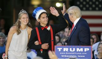 Republican presidential candidate, businessman Donald Trump high-fives homecoming king Austin Cook as queen Eylse Pescott, left, looks on during a rally at Urbandale High School, Saturday, Sept. 19, 2015, in Urbandale, Iowa. (AP Photo/Charlie Neibergall) ** FILE **