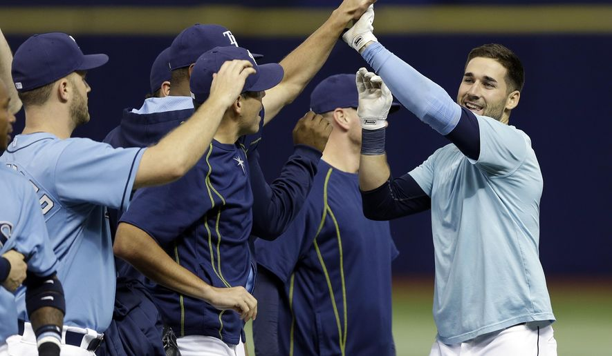 Tampa Bay Rays' Kevin Kiermaier, right, celebrates with teammates after his walk-off RBI single off Baltimore Orioles relief pitcher Zach Britton during the ninth inning of a baseball game Sunday, Sept. 20, 2015, in St. Petersburg, Fla. Rays' Evan Longoria scored the game-winning run in the Rays 7-6 victory. (AP Photo/Chris O'Meara)