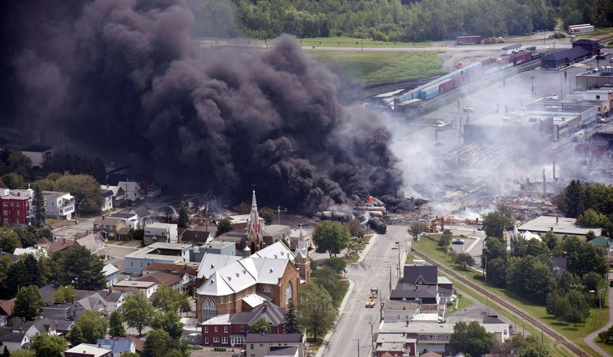 FILE - In this July 6, 2013, file photo, smoke rises from railway cars from now defunct Montreal, Maine & Atlantic Railways company that were carrying crude oil after derailing in downtown Lac Megantic, Quebec, Canada. A settlement for victims of a fiery train derailment that claimed multiple lives is poised for final approval, but payments could be held up by a court challenge in Canada. (Paul Chiasson/The Canadian Press via AP) MANDATORY CREDIT