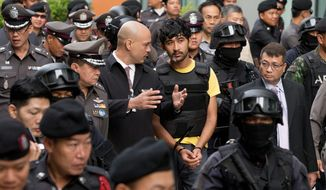 Police officers escort a key suspect in last month's Bangkok bombing. Identified by Thai police as Yusufu Mieraili, the suspect was traveling on a Chinese passport, but his nationality remains unconfirmed. (Associated PRess)