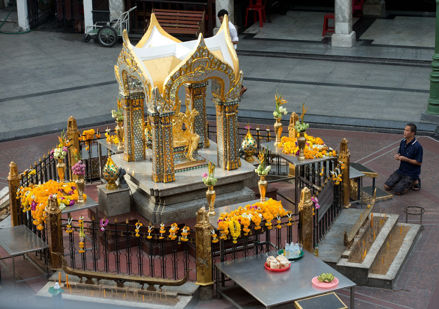 A visitor makes an offering for Phra Phrom, the Thai interpretation of the Hindu god Brahma at the Erawan Shrine, the scene of the Aug. 17 bombing, in Bangkok, Wednesday, Sept. 9, 2015. Thai police have escorted one of the key suspects in last month's deadly Bangkok bombing to the scene of the attack  Wednesday, for a public re-enactment of his alleged crime that left 20 people dead and and more than 120 injured. (AP Photo/Mark Baker)