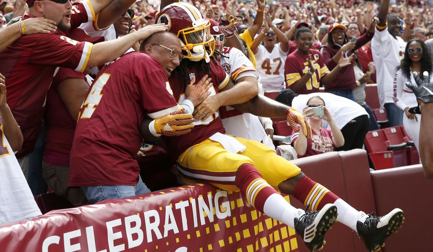 Washington Redskins running back Matt Jones jumps into the fans after scoring a touchdown during the first half of an NFL football game against the St. Louis Rams in Landover, Md., Sunday, Sept. 20, 2015. (AP Photo/Alex Brandon)