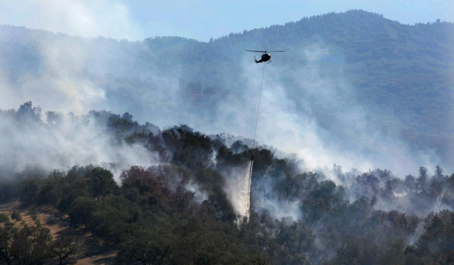 A helicopter makes a water drop on a wildfire hot spot Sunday, Sept. 20, 2015, in Carmel Valley, Calif. The blaze burning north of the community of Jamesburg quickly grew after starting Saturday afternoon, the California Department of Forestry and Fire Protection said. (Vern Fisher/The Monterey County Herald via AP) MANDATORY CREDIT