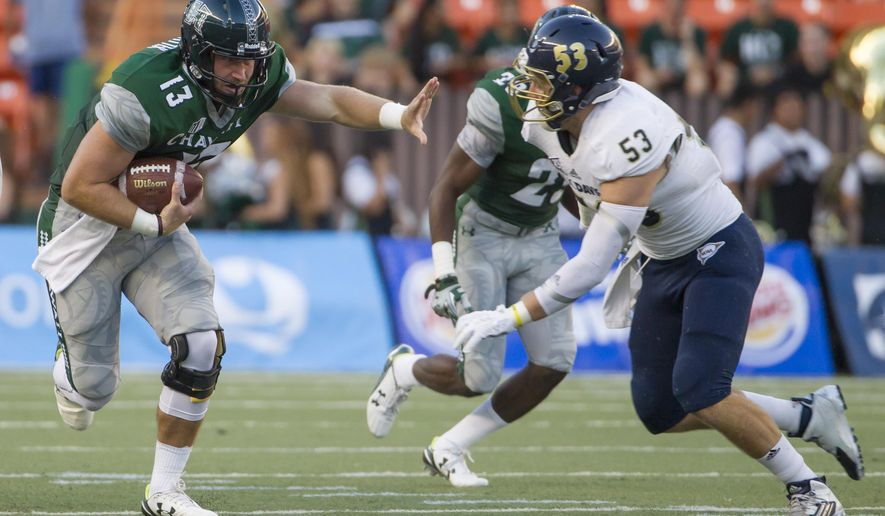 Hawaii quarterback Max Wittek (13) attempts to stiff arm UC Davis linebacker Russell Reeder (53) in the first half of an NCAA college football game, Saturday, Sept. 19, 2015, in Honolulu. (AP Photo/Eugene Tanner)