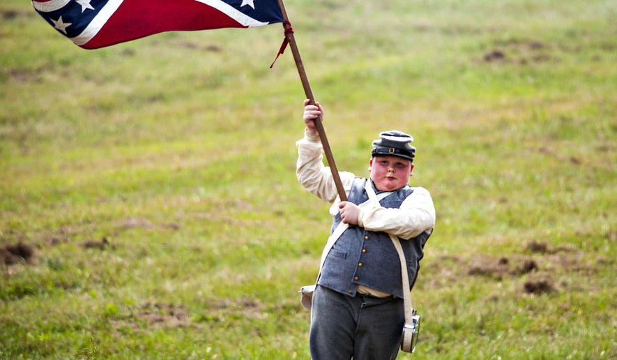 In this Sept. 12, 2015, photo Daniel Bowman, 12, waves a Confederate flag during the Hart County Civil War Days historical re-enactment of the Battle of Munfordville in Munfordville, Ky. (Miranda Pederson/Daily News via AP) MANDATORY CREDIT