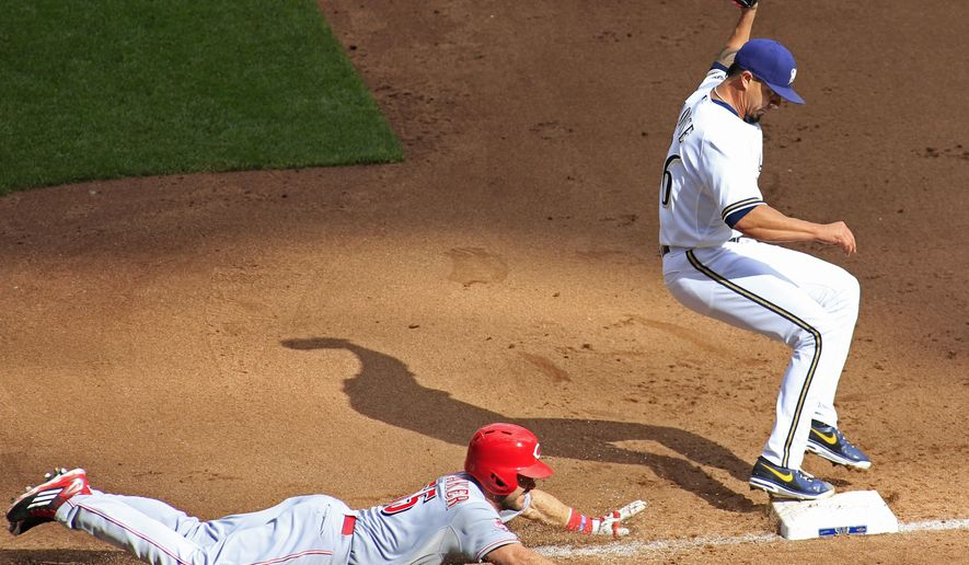 Milwaukee Brewers pitcher Kyle Lohse, right, gets the force out at first base against Cincinnati Reds' Skip Schumaker, left, during the sixth inning of a baseball game, Sunday, Sept. 20, 2015, in Milwaukee. (AP Photo/Darren Hauck)