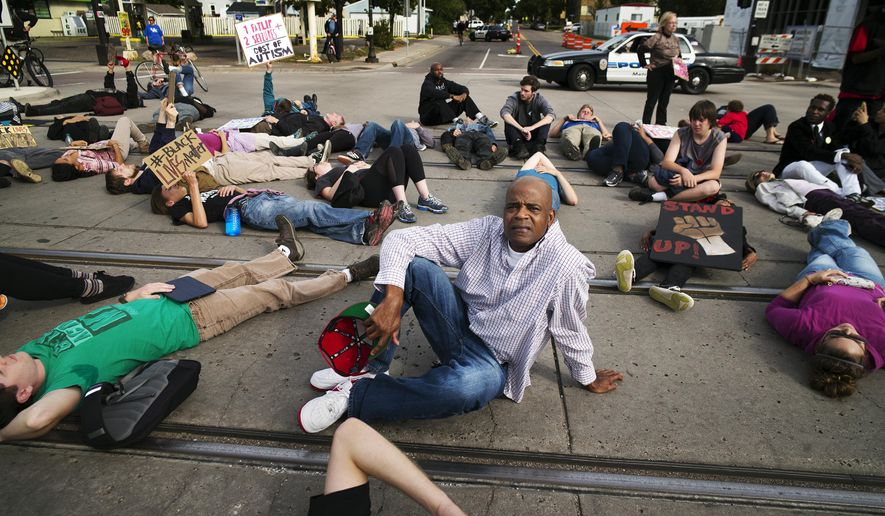 Near the Lexington light rail station in St. Paul, Minn., protesters with Black Lives Matters block traffic to and from TCF Bank Stadium before an NFL football game between the Minnesota Vikings and the Detroit Lions on Sunday, Sept. 20, 2015. Black Lives Matter St. Paul staged a die-in on the Green Line light-rail tracks to protest what they consider excessive force by Metro Transit police officers who arrested a boy with autism there Aug. 31. (Richard Tsong-Taatarii/Star Tribune via AP)  MANDATORY CREDIT; ST. PAUL PIONEER PRESS OUT; MAGS OUT; TWIN CITIES LOCAL TELEVISION OUT