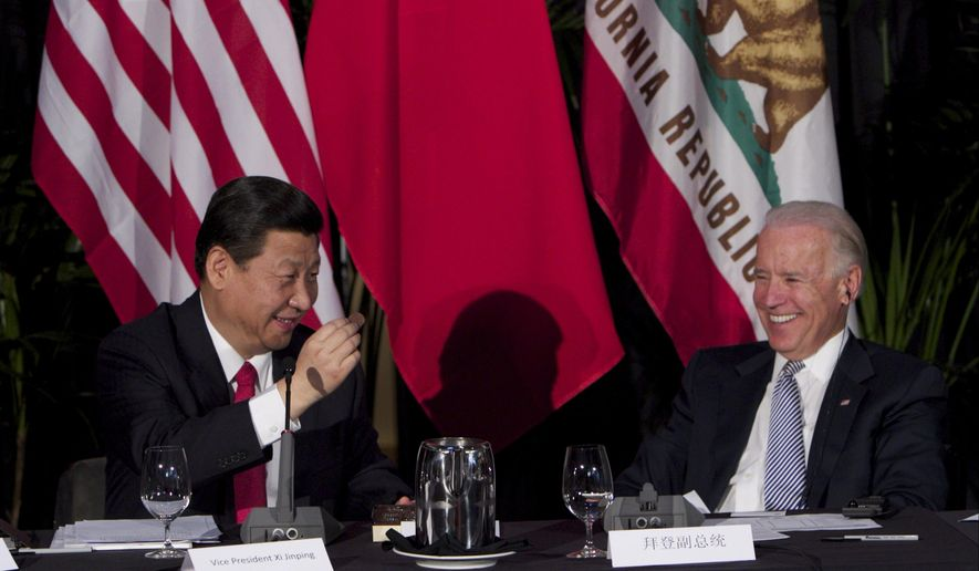 In this Feb. 17, 2012, file photo, Xi Jinping, China's president and Communist Party chief, left, eats Hawaiian macadamia chocolate gifted by Governor of Hawaii, Neil Abercrombie, not seen, during a governors meeting held inside the Walt Disney Concert Hall as then-Vice President Joe Biden, right, looks on in Los Angeles. (AP Photo/Damian Dovarganes, File)