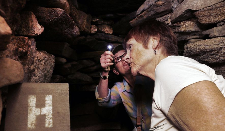 "In this photo taken Tuesday, Sept. 15, 2015, Marie St. Onge, right, and Carol Stevens examine the rock formations inside the ""Oracle"" chamber at what is called America's Stonehenge, in Salem, N.H. The 1-acre grouping of rock configurations has drawn believers to say it is thousands of years old. Skeptics say the evidence suggests it was put together by a 19th century shoemaker.  (AP Photo/Jim Cole)"